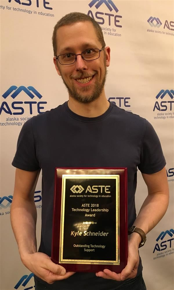 Student Support Specialist Kyle Schneider holds his award.