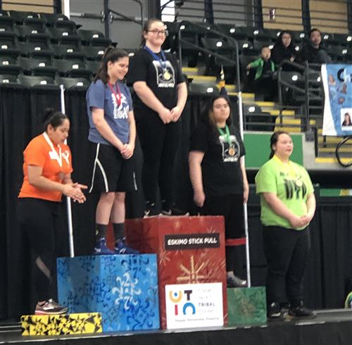 Students stand on the awards podium for Girls Eskimo Stick Pull.