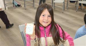 "A student holds up a cookie shaped like a piece of paper that reads, ""Back to school""."