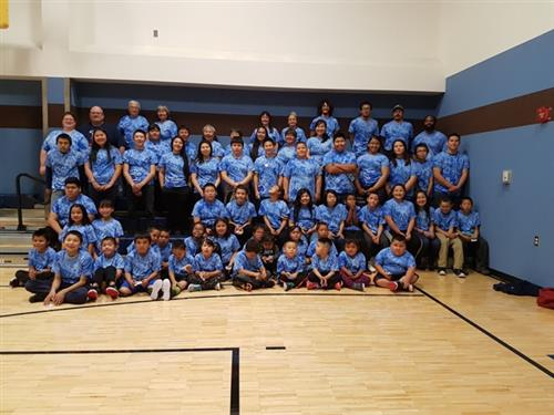 Students and staff pose in their school t-shirts