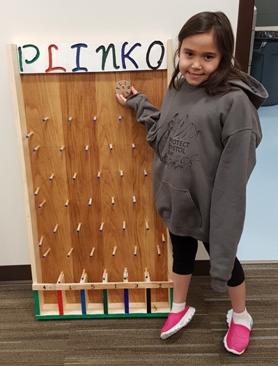 A student poses in front of a homemade plinko board.