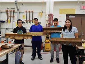 Students displaying coat racks made in woodworking class.