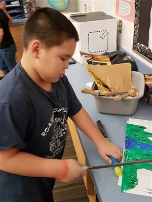 Student cutting the groove on his ice fishing pole