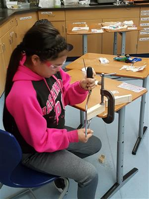 Student using coping saw to shape pinewood derby car
