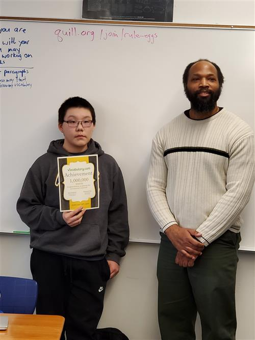 student with certificate standing with teacher