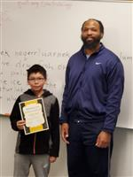 boy and teacher pose with certificate