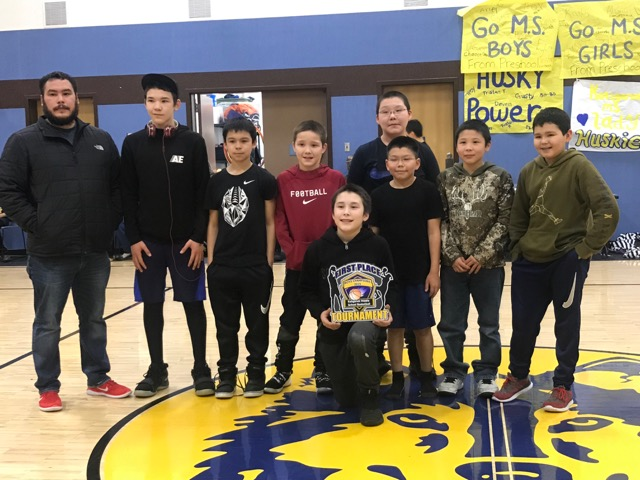 Koliganek Middle School boys Basketball team poses with their coach and trophy.