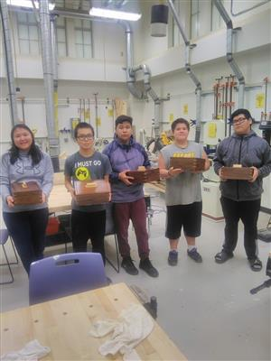 5 shop students holding the jewelry box they made