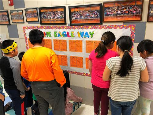 Students review the Positive Referral bulletin board