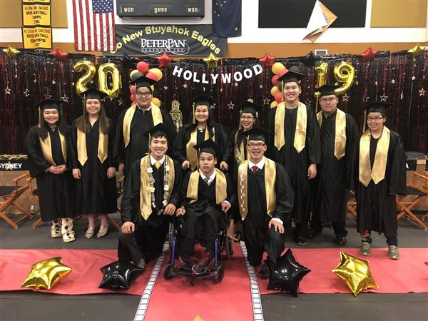 Group of 11 graduating seniors in front of Hollywood themed graduationd decorations.